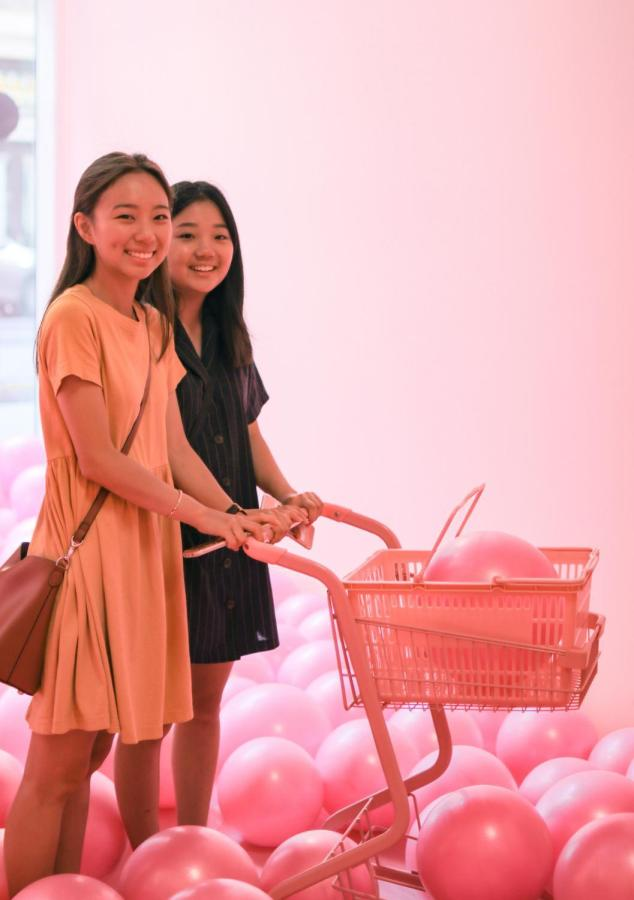 Two visitors stand among pastel-colored balloons.