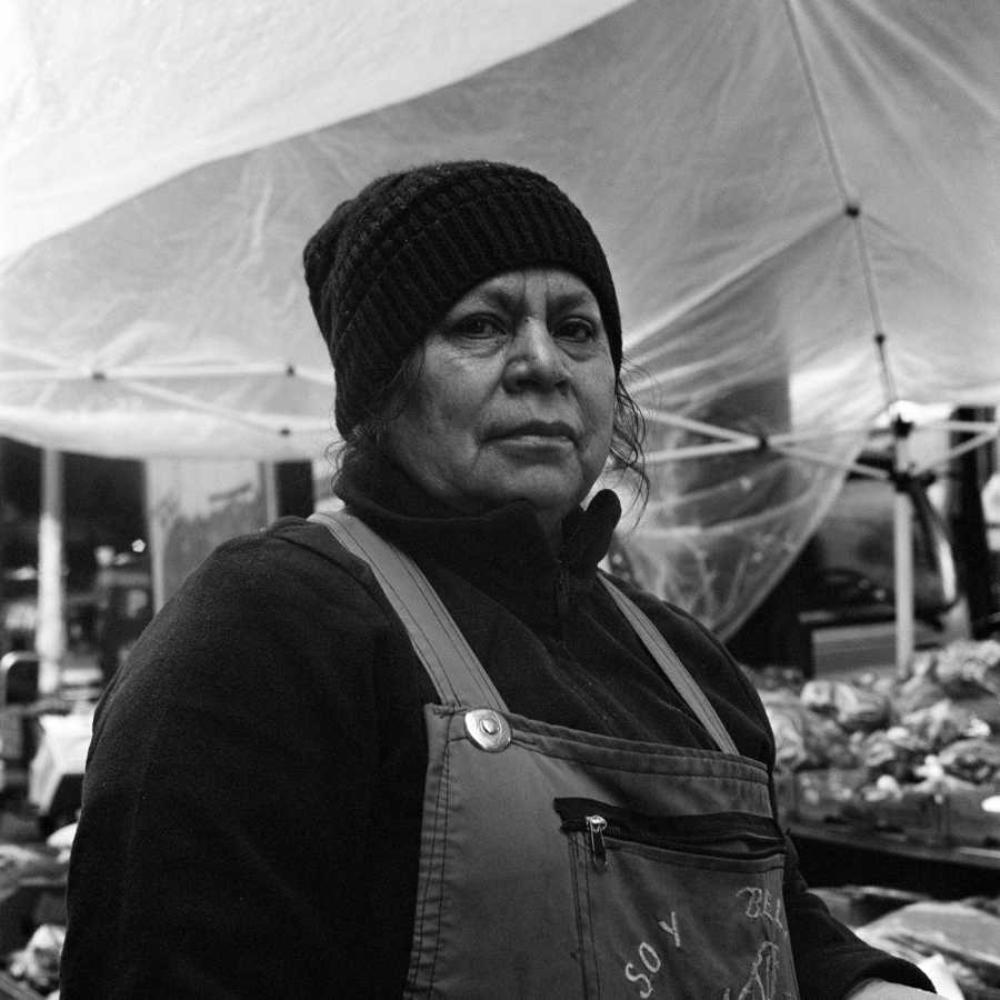 She was working at a produce stand on the street when I asked to take her picture. She kept working but agreed and only stopped working to look up at the camera for a moment.