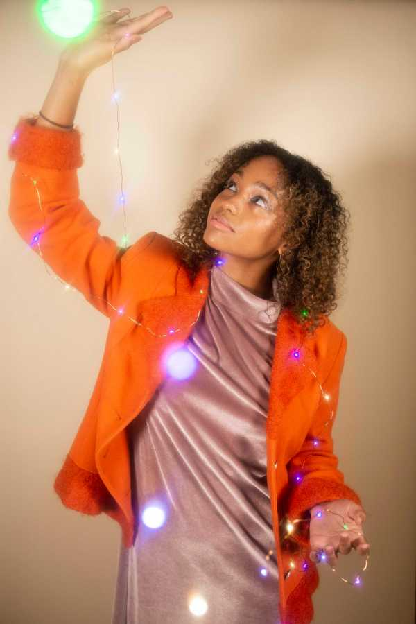 ALL OF THE LIGHTS | Caira wearing Madewell velvet lavender mock neck dress and Chenille orange blazer. (Photo by Katie Peurrung)