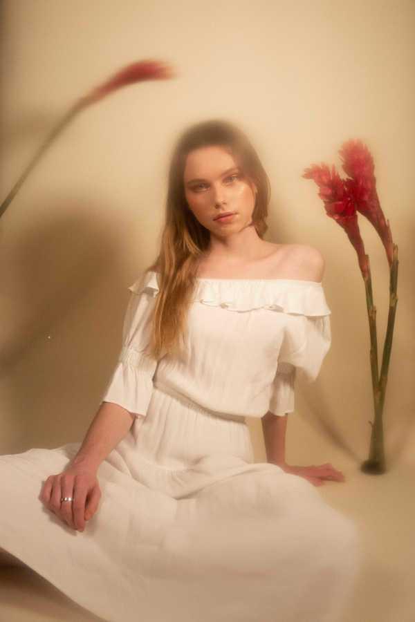 BETWEEN TWO FERNS | Caroline wearing Vestire white off-the-shoulder prairie dress. (Photo by Katie Peurrung)