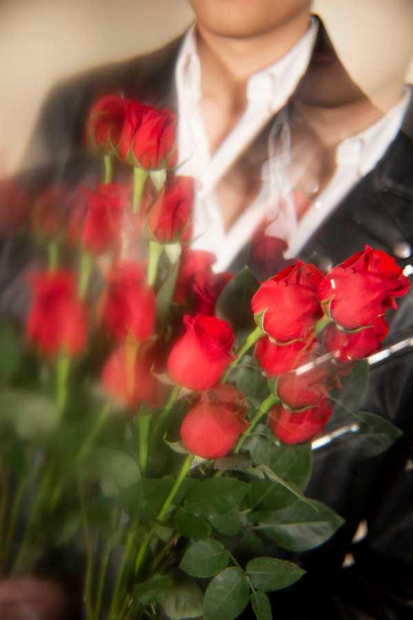 MULTIPLICITY | Joseph holds a bouquet of a dozen roses. (Photo by Katie Peurrung)