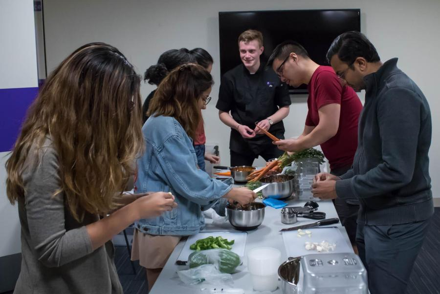 Steinhardt+first-year+Abe+Konick+%28center%29+teaches+a+group+of+students+how+to+cook+spaghetti+sauce+at+the+first+Open+Kitchen+event+of+the+semester.+%28Photo+by+Victor+Porcelli%29