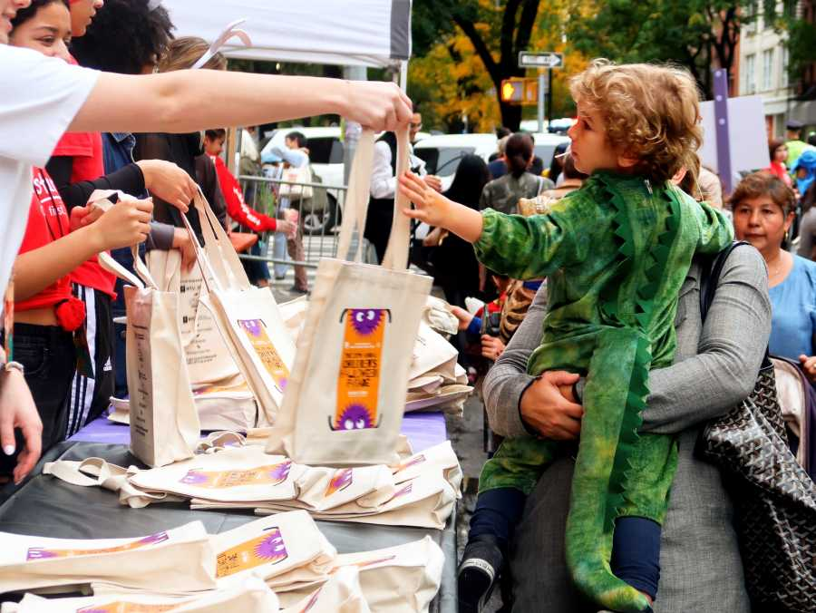Pictured is little boy dressed as a dinosaur receiving a free trick-or-treat bag. On Halloween Thursday, the annual Children's Halloween Parade took Place at Washington Square Park (Staff Photo by Chelsea Li)