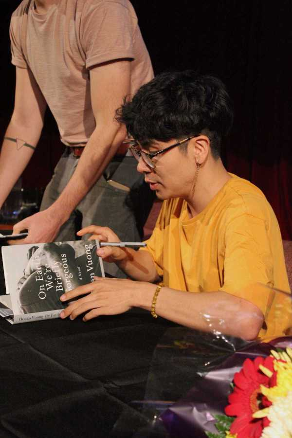 Ocean Vuong opens the pages of his book On Earth We're Briefly Gorgeous to sign his autograph. On Tuesday, the Asian/Pacific/American Institute at NYU welcomed the award-winning writer and poet as its 2019-20 Artist-in-Residence. (Staff Photo by Emma Li)