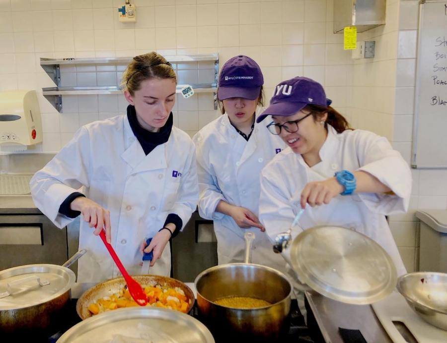 Instructors in the Food Lab help a student with the recipe she must complete in class. The Steinhardt class is a hands-on course that exposes students to a variety of culinary techniques. (Photo by Madison San Miguel)