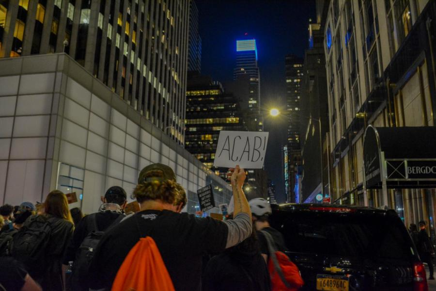 A protester holds up a sign reading