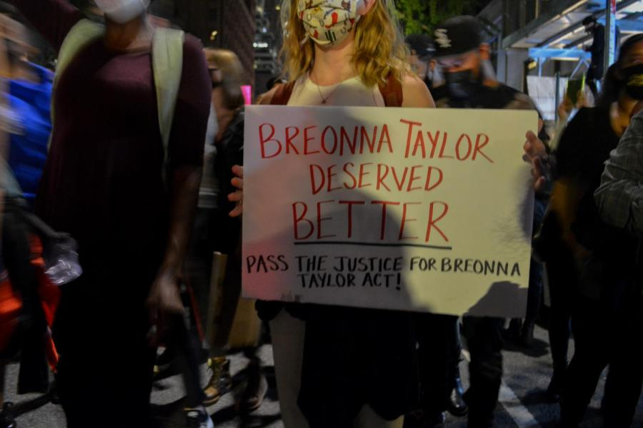 A protester holds a sign reading