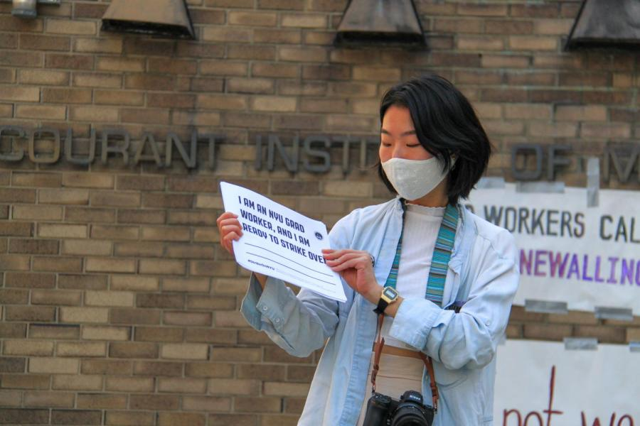 GSOC member Yuwei passes out papers for rally-goers to fill out in support. (Staff Photo by Alexandra Chan)