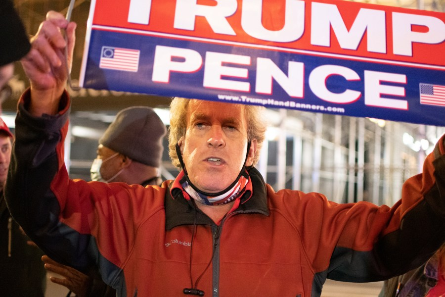 A Trump supporter holds a Trump Pence poster at a rally in midtown on election night 2020. Trump left a legacy in the Republican Party. (Staff Photo by Jake Capriotti)