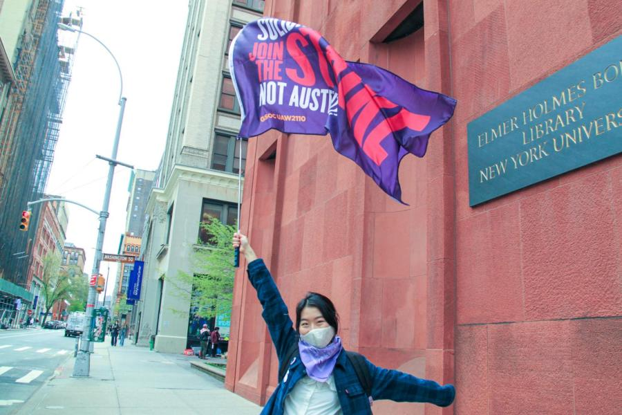 NYU GSOC member Yuwei waves a flag that reads