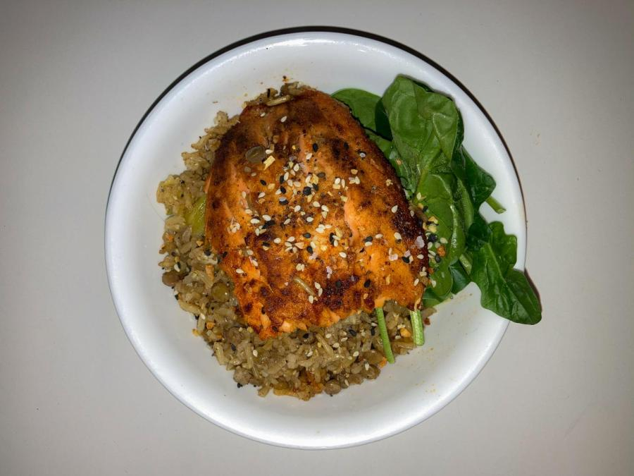 This grain bowl has a base of brown rice and lentils and is served with sautéed onions, broccoli, and pan-seared salmon on a bed of spinach. Taking up a sustainable diet does not mean it has to be plant-based as there is no one solution to climate change as long as you're mindful about your consumption and its impact on the environment. (Staff Photo by Gabby Lozano)