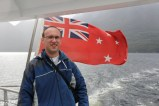 Philip by the New Zealand naval flag on the back of our Doubtful Sound ship, the Patea Explorer.
