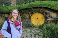 Jessica all smiles by a yellow hobbit door