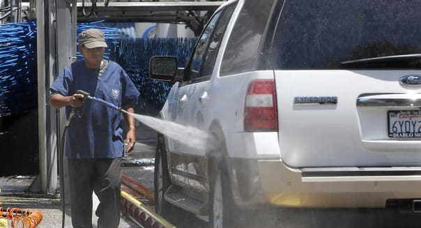 FILE - In this June 24, 2015, file photo, a worker washes a car at Bob's Car Wash in Roseville, Calif. The Labor Department releases third-quarter productivity data on Thursday, Nov. 5, 2015. (AP Photo/Rich Pedroncelli, File)
