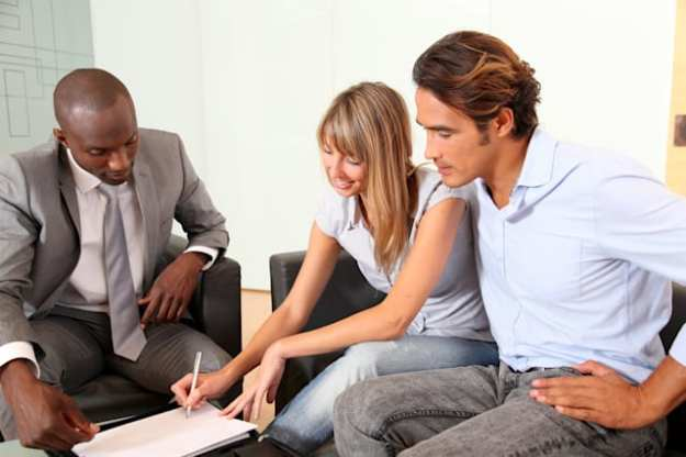 couple signing home purchase...