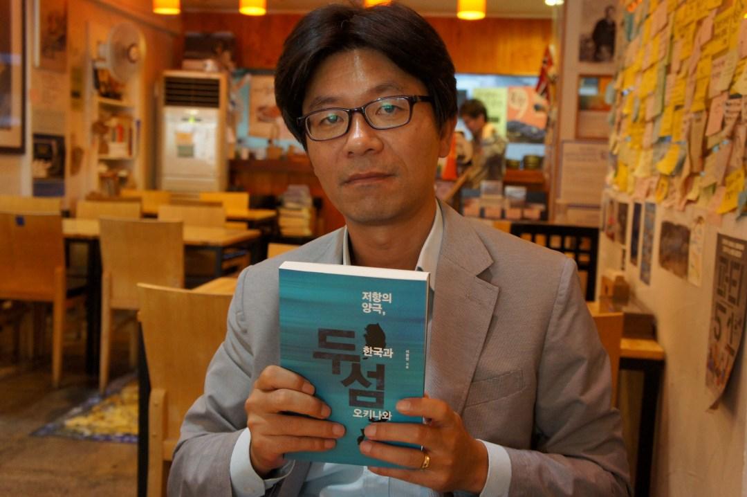 著書を手にする李明元さん。文在寅(ムン・ジェイン)大統領の母校として知られる慶煕(キョンヒ)大学校で教授を務めている。「沖縄と韓国の交流がもっと必要」と話した=9月2日、ソウル市