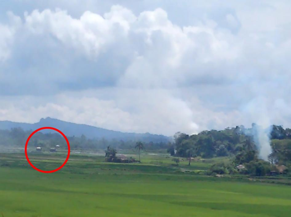 A screen grab of a video shows two dark-colored Burmese military trucks within several hundred meters of a burning village. © 2017 Private