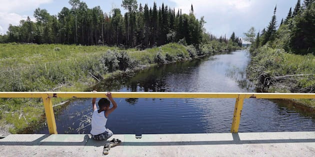 A boy from the Shoal Lake 40 First Nation sits on a bridge over a channel on June 25, 2015.