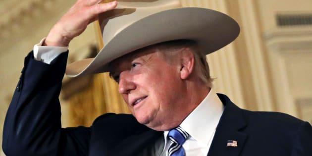U.S. President Donald Trump wears a cowboy hat as attends a