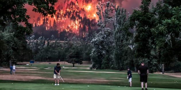El bosque de Eagle Creek arde mientras múltiples golfistas juegan en el Campo de Golf Beacon de North Bonneville, en Washington, EEUU, el cuatro de septiembre de 2017.