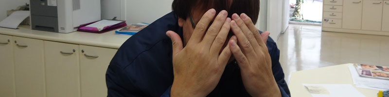 business man hiding his face in shame