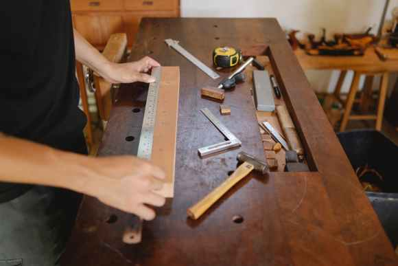 man working with wood and ruler in carpentry studio