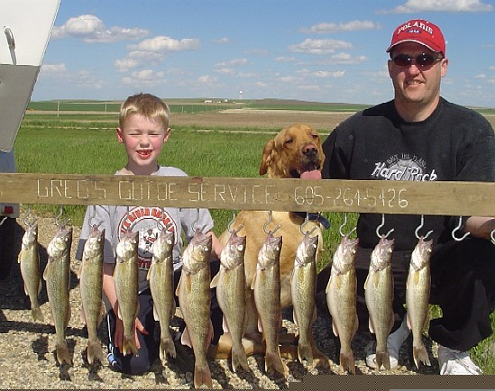 Father, Son and dog Sage posing with their catch of walleye