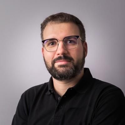 Portrait de Yoann PIERRE souriant avec une barbe et des lunettes