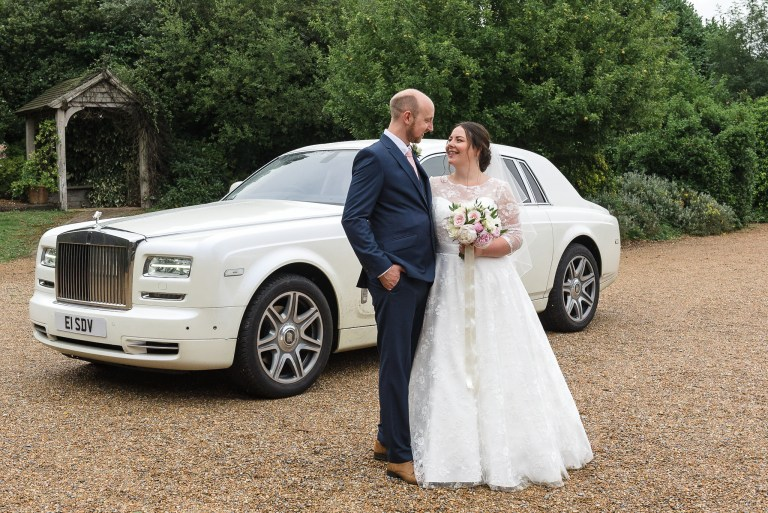 Bride and groom posing in front of their white Rolls Royce wedding car at Swallows Oast, Ticehurst, East Sussex | Oakhouse Photography