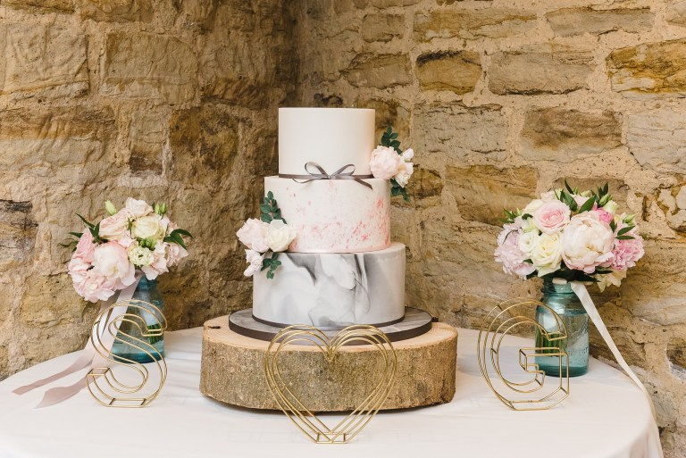 Wedding cake and floral bouquets on display at Swallows Oast wedding venue, Ticehurst, East Sussex | Oakhouse Photography