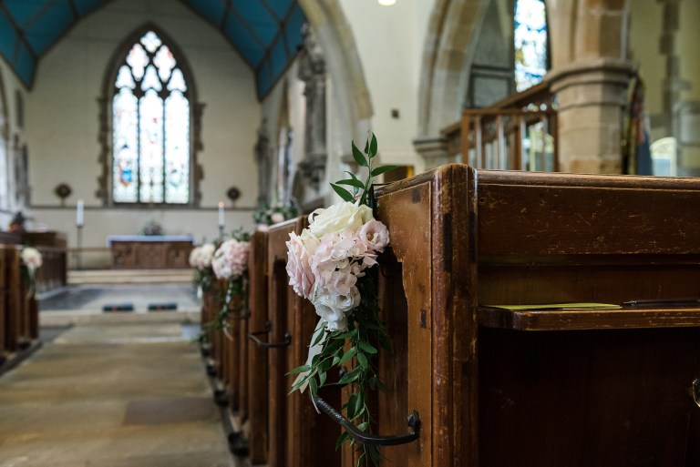 Wedding flowers on the pews at Wadhurst Church, Wadhurst, East Sussex | Oakhouse Photography
