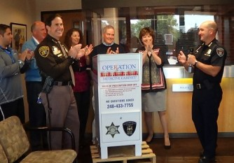Oakland County Sheriff and partners standing next to an Operation Medicine Cabinet drop-off box.