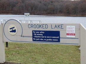 A lake with a gray sign in front of it that reads: Crooked Lake.