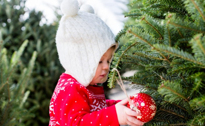 Cute baby girl in red Scandinavian dress at the Christmas tree farm.