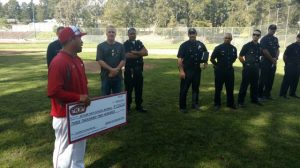 Skyline Baseball Coach James Salazar Accepts a Donation from Oakland Firefighters in Honor of Jake Walter.
