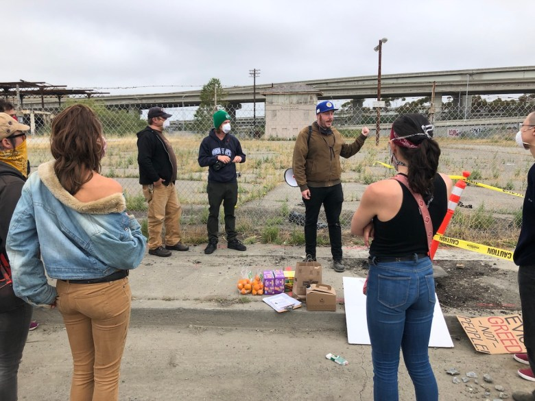 A group of people stand in a circle outside, with the freeway in the background