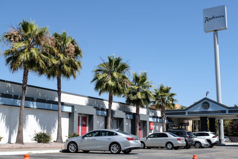 short, long white building with a parking lot and palm trees