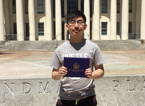 Andrew Nham holding his diploma in front of Oakland Technical High School.