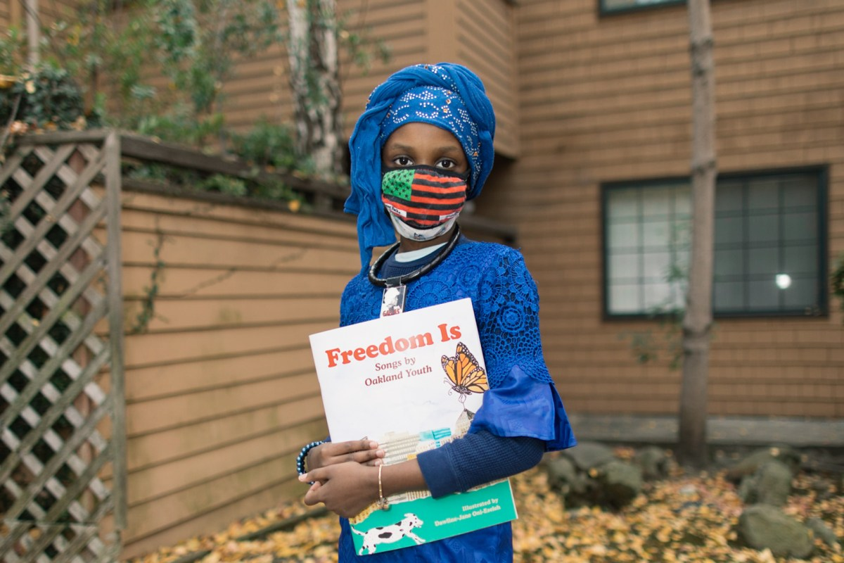 "A youth writer named Nafissatou Ndiaye holding a copy of ""Freedom Is,"" a companion book to a musical album of the same name, produced by the nonprofit Chapter 510"