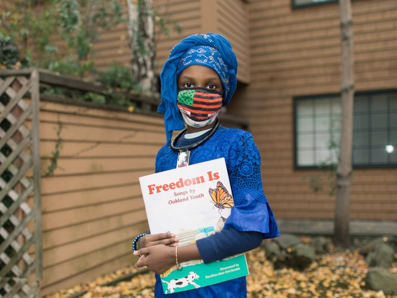 """A youth writer named Nafissatou Ndiaye holding a copy of """"Freedom Is,"""" a companion book to a musical album of the same name, produced by the nonprofit Chapter 510"""