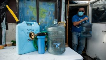 Jugs of water and equipment on a table. A masked man comes out of a makeshift shack carrying another.