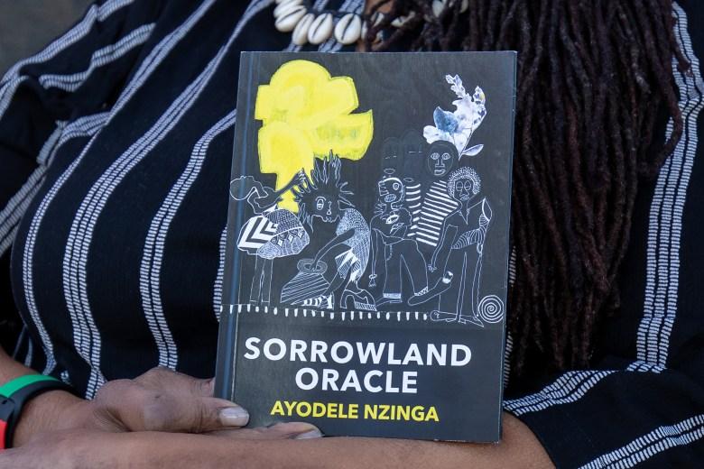 "Ayodele Nzinga holds her new book of poetry, ""Sorrowland Oracle""."