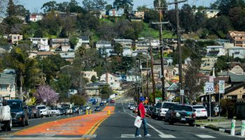A pedistrian crosses the street at 90th Ave in East Oakland. Some of the Oakland hills can be seen in the distance.
