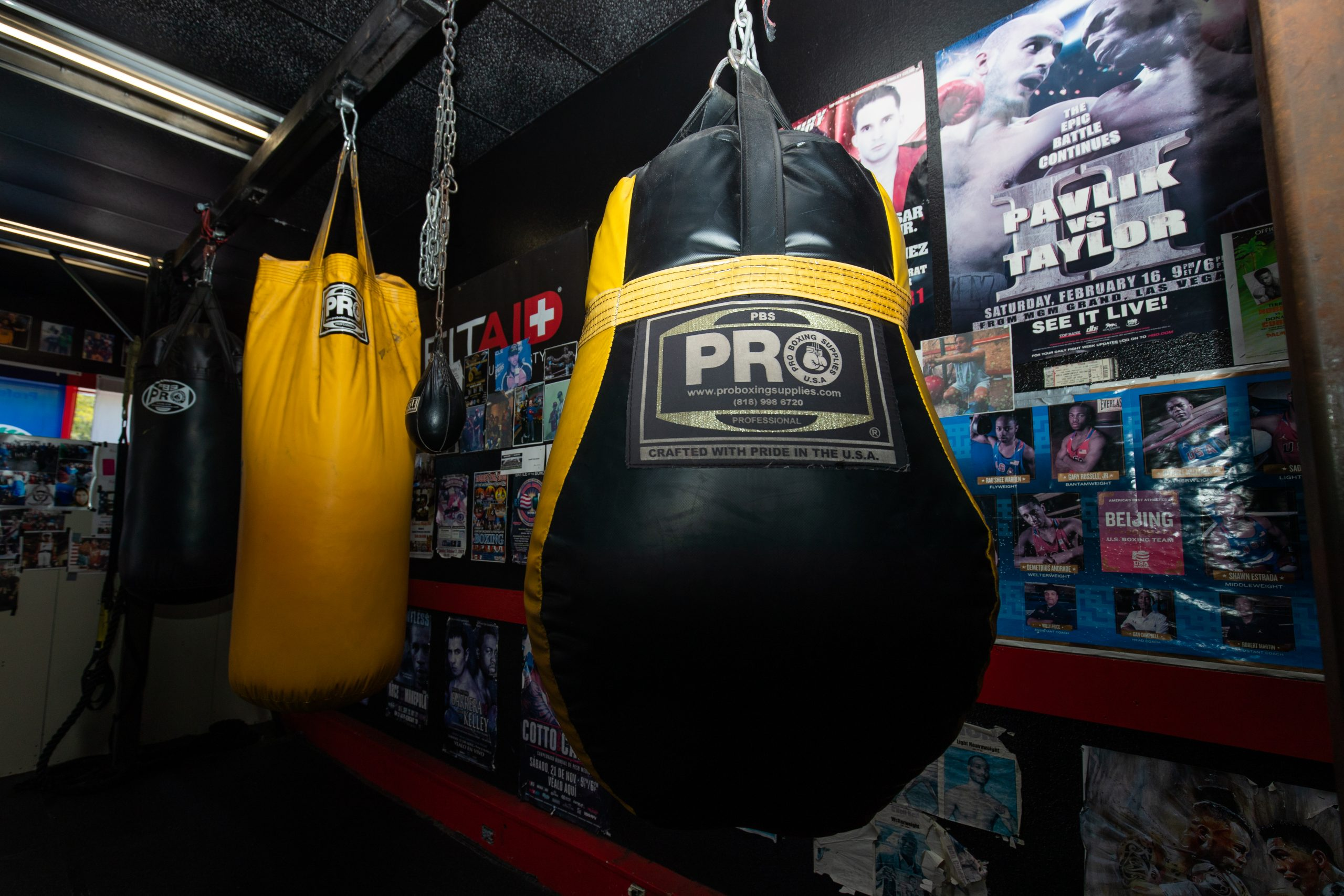 Punching bags hang from the ceilings amongst more posters of boxers and fight events.