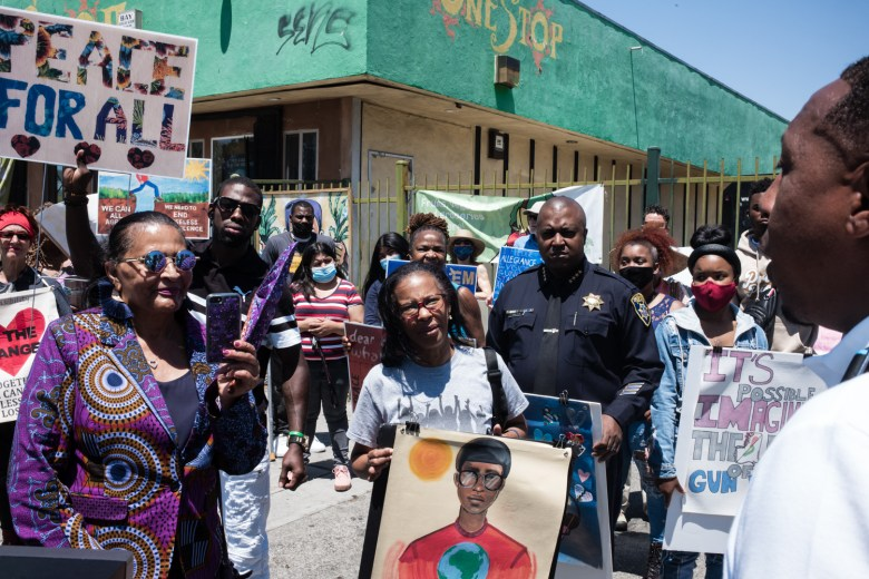 Daryle Allums speaking to a small group that gathered underneath the Adamika Village Banner on 84th Avenue and International Boulevard in Oakland on Saturday, June 26, 2021.