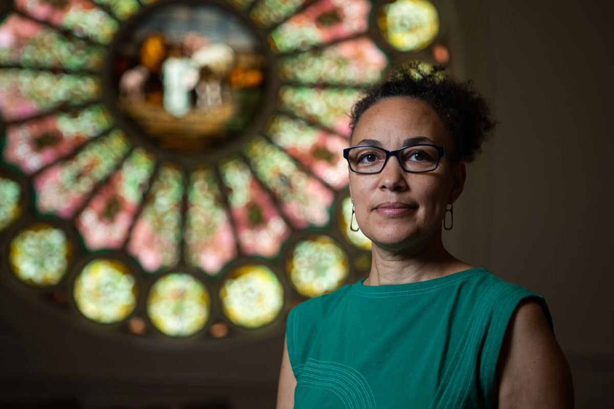 Ariana Makau, founder of Nzilani Glass Conservation, a stained glass preservation company, in front of a recent restoration project at Resurrection Church Oakland.