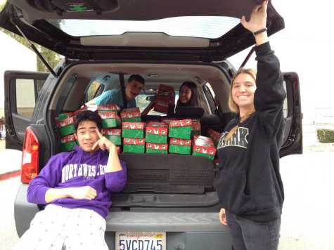 Key Club members Lucas Hsiong, Nathaniel Driggs, Jayda Nalamlieng and Tyler Smith load gifts to be delivered to children worldwide (Irena Yang/Talon).