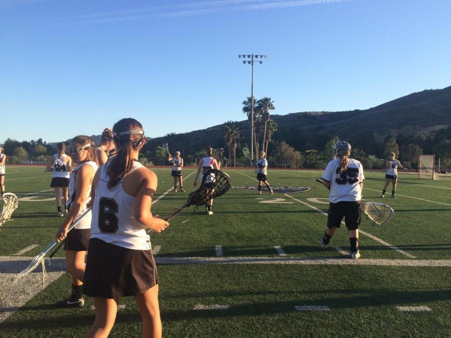 The girls' lacrosse team practices before winning against West Ranch on Senior Night. The team has been dominant this season (Carly Albert/Talon)