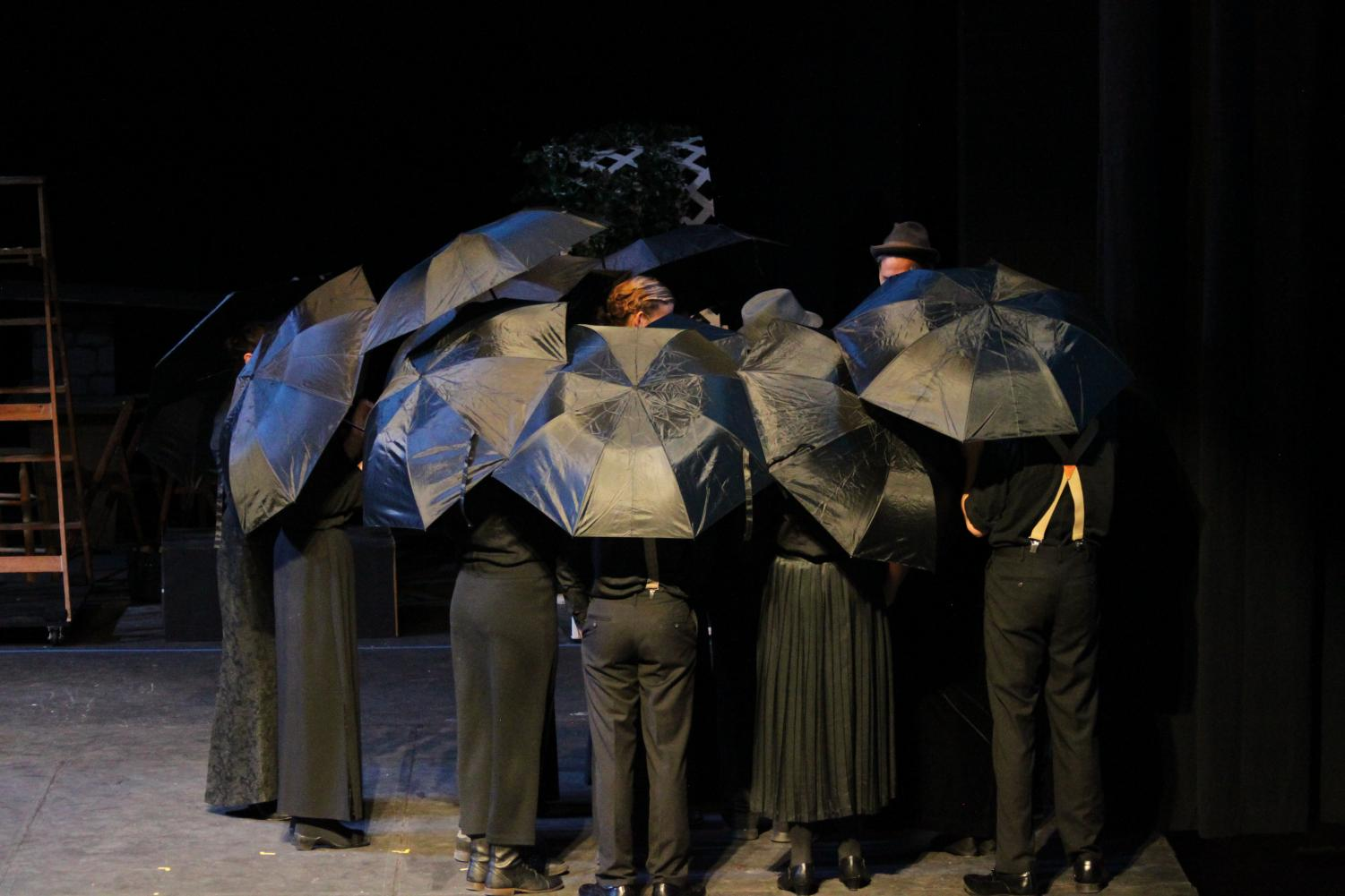 Student drama members huddle during a funeral in 'Our Town.'
