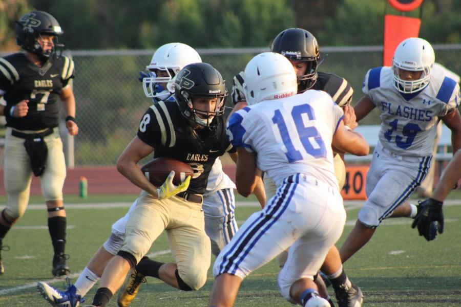 Junior varsity player charges for a tackle